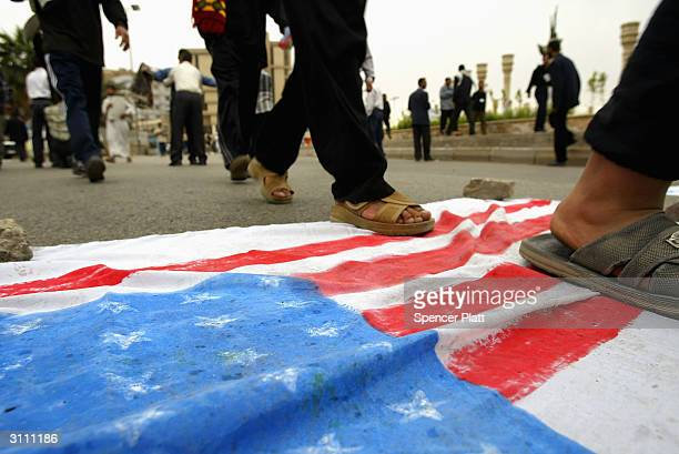 Men walk over a homemade American Flag as a sign of disrespect March 19 2004 in Baghdad Iraq A year ago this weekend bombs began dropping on Baghdad...