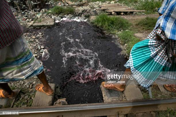 Men walk over dye and polluted water that is being released into a canal that leads to the Buriganga river in Shyampur June 10 2018 in Dhaka...