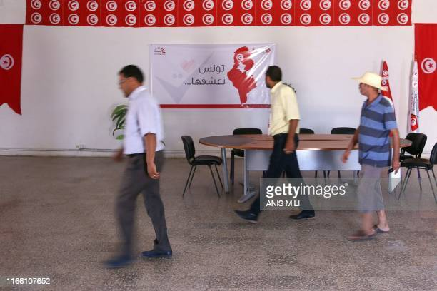 Men walk past a banner reading Tunisia we adore it inside a branch of the Independent High Authority for Elections on August 15 in the central...