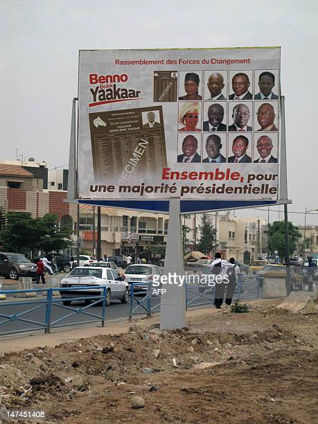 Men walk past a bilboard showing a campaign advertisement for the Benno Book Yaakaar coalition ruling party in the upcoming legislative elections, on...