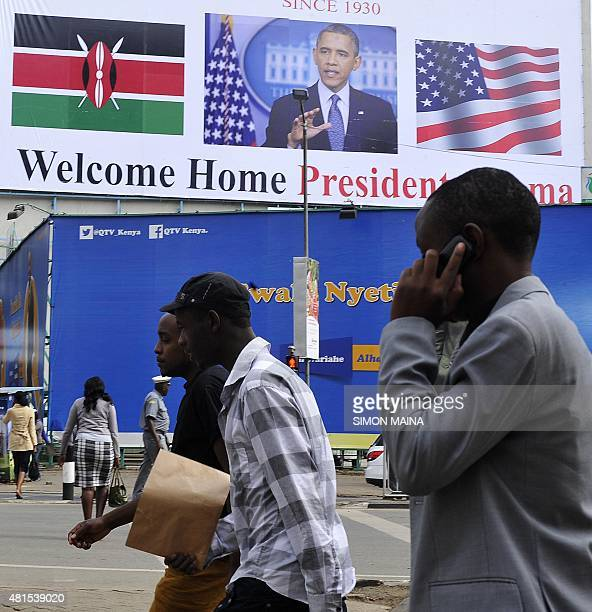 Men walk past a billboard welcoming US President Barack Obama on July 22 2015 in Nairobi ahead of his visit Obama will make his first presidential...