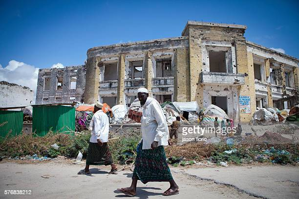 Men walk past a camp for Internally Displaced Persons in a destroyed building in Mogadishu