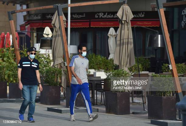 Men walk past a closed restaurant in the Saudi capital Riyadh, on February 5 after new rules laid out by the Ministry of Interior to curb a recent...