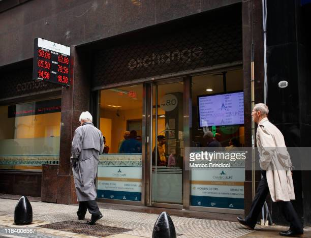 Men walk past a currency exchange house showing updated prices of Dollars Brazilian reais and Euros on October 28 2019 in Buenos Aires Argentina...