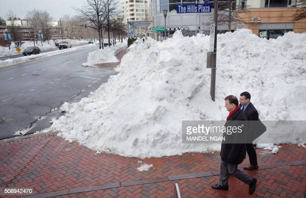 Men walk past a large mound of snow in Chevy Chase Maryland on January 26 2016 / AFP PHOTO / Mandel Ngan