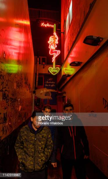 Men walk past a luminous sign advertising a lap dancing bar in the Red Light District on April 12 2019 in Amsterdam The Netherlands Amsterdam is...
