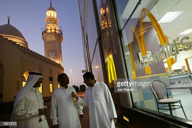 Men walk past a McDonald's as they leave a prayer session in a mosque November 10 2002 in Manama Bahrain McDonald's Corporation announced that it...