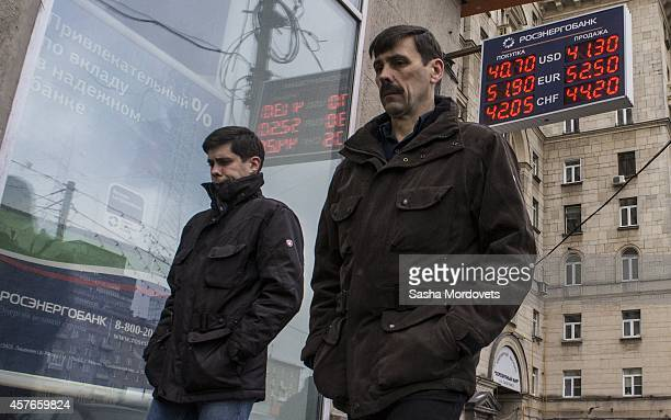 Men walk past a money exchange office as it is reported that the Russian rouble has weakened on October 22 2014 in Moscow Russia Russia's currency...