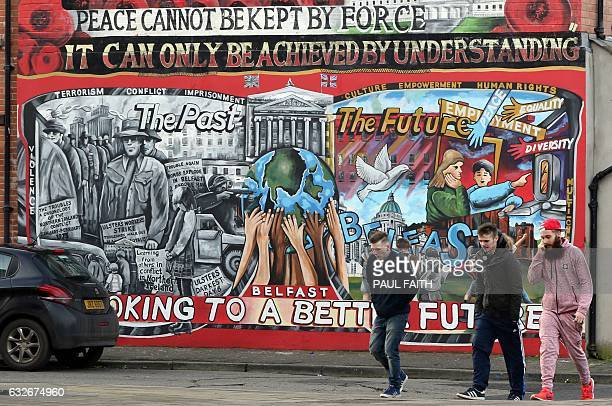 Men walk past a mural on the Newtownards Road in Belfast on January 25 2017 Northern Ireland will hold snap elections on March 2 2017 in a bid to...