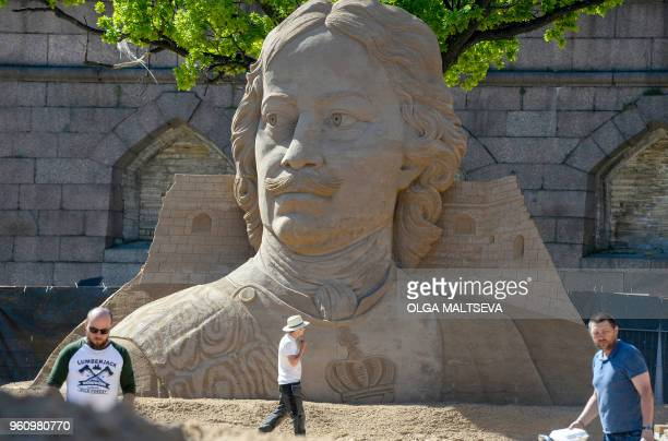 Men walk past a sand sculpture featuring Tsar Peter the Great as preparations are under way for a sand sculpture festival by the wall of the St Peter...