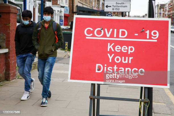 Men walk past a sign reading 'COVID-19, Keep your distance' in London.