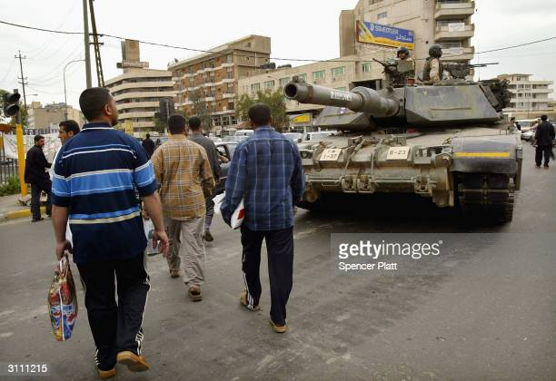 Men walk past a US Army tank after Friday prayers March 19 2004 in Baghdad Iraq A year ago this weekend bombs began dropping on Baghdad as the...