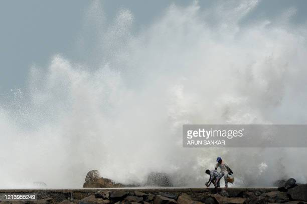 Men walk past as waves hit a breakwater at Kasimedu fishing harbour in Chennai on May 19 as Cyclone Amphan barrels towards India's eastern coast...