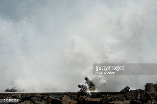 TOPSHOT Men walk past as waves hit a breakwater at Kasimedu fishing harbour in Chennai on May 19 as Cyclone Amphan barrels towards India's eastern...