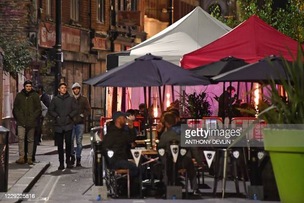 Men walk past bars on Dale Street in Manchester city centre northwest England on October 22 2020 ahead of new coronavirus restrictions coming into...