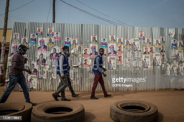 Men walk past election posters in Kampala. Uganda's elections are expected to take place early next year.