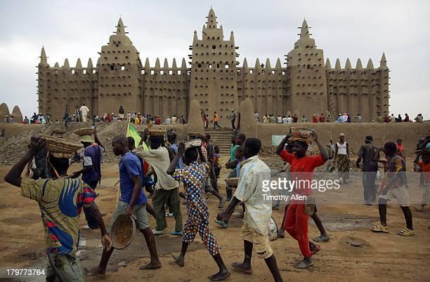 Men walk past Great Mosque, Djenne, Mali