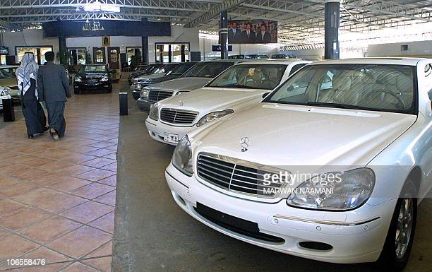 Men walk past Mercedes cars displayed at the Sardar dealership in Baghdad's alNahda suburb 22 December 2002 Under the socalled UN oilforfood program...