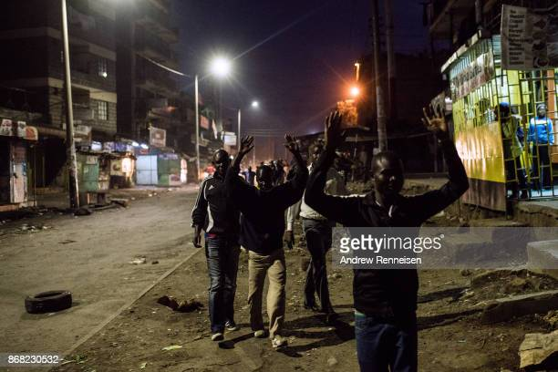 Men walk past police during unrest after election results were announced in the Mathare slum on October 30 2017 in Nairobi Kenya Uhuru Kenyatta was...