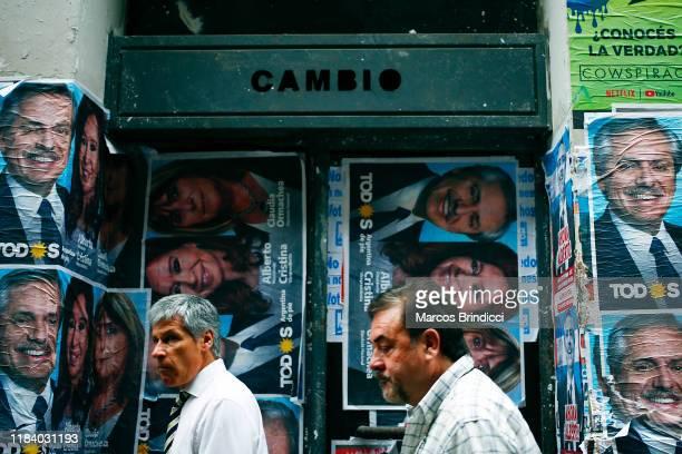 Men walk past posters advertising winning ticket of Frente de Todos represented by Alberto Fernandez and Cristina Fernandez on October 28 2019 in...