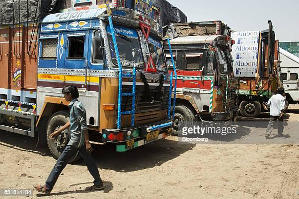 Men walk past trucks in a parking bay area of a highway service station on National Highway 8 in Haryana India on Saturday May 14 2016 Rivigo...