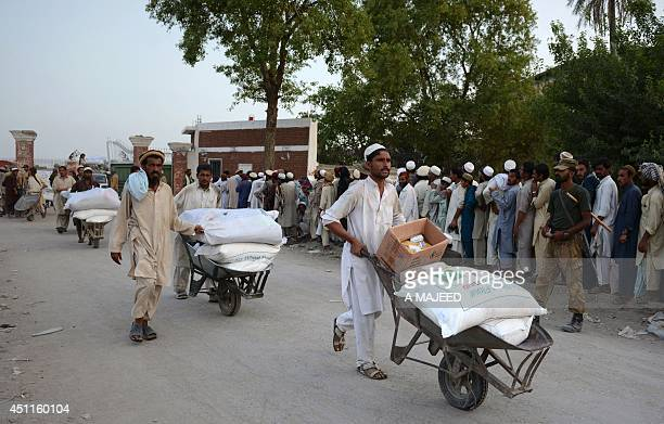 Men walk past with wheelbarrows of provisions as Pakistani IDPs from the North Waziristan region gather outside of the World Food Programme food...