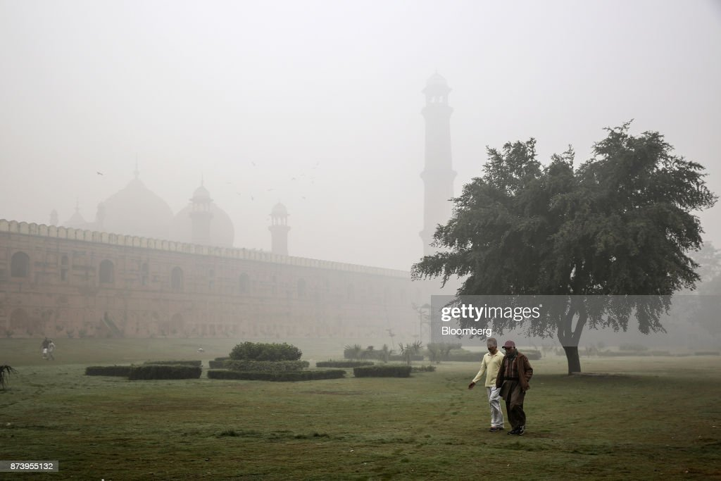Men walk though Iqbal Park shrouded in smog in Lahore Pakistan on Tuesday Nov 14 2017 The fates of 15 billion people in both India and Pakistan are...