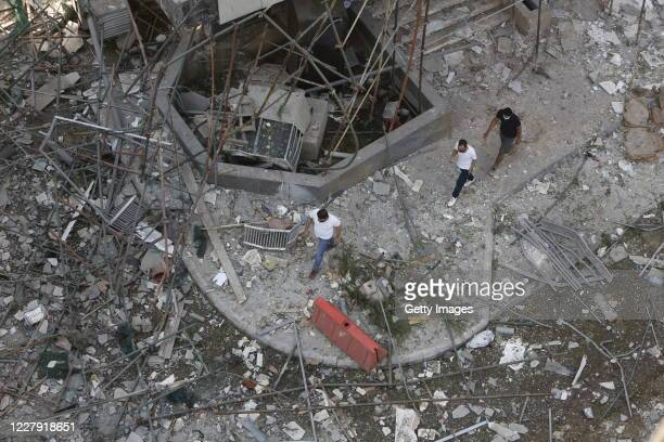 Men walk through a debris-covered street, damaged by an explosion a day earlier, on August 5, 2020 in Beirut, Lebanon. As of Wednesday morning, more...