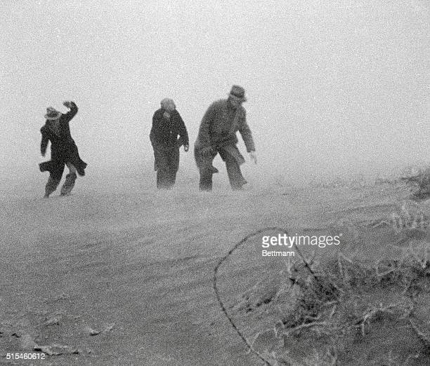 Men walk through a dust storm in Garden City Kansas during the Dust Bowl Agricultural damage caused by deep plowing no crop rotation and lack of...
