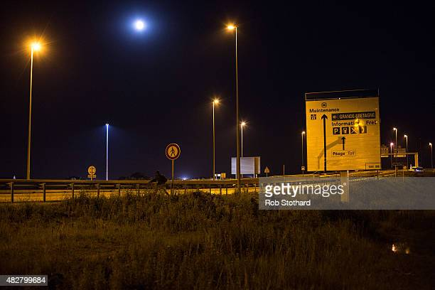 Men walk through a field near the Eurotunnel terminal in Coquelles on August 3 2015 in Calais France Hundreds of migrants are continuing to attempt...