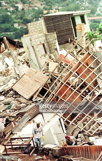 Men walk through the rubble of destroyed homes in the La Soto neighborhood 04 November which was almost completely wiped out by a landslide 01...