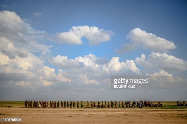 Men walk towards an area controlled by fighters of the US-backed Syrian Democratic Forces after leaving the Islamic State group's last holdout of...