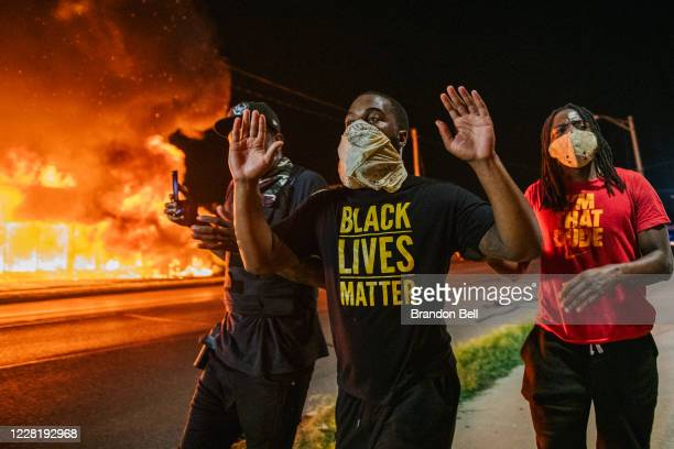 Men walk towards law enforcement with their hands up on August 24 2020 in Kenosha Wisconsin A second night of civil unrest occurred after the...