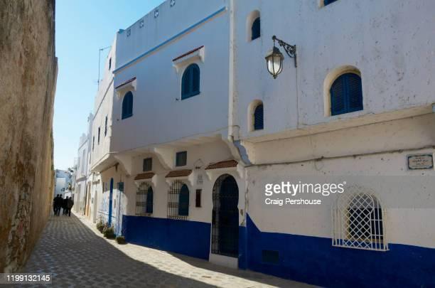 men walking along alley between city wall and whitewashed houses in asilah's medina. - only men stockfoto's en -beelden
