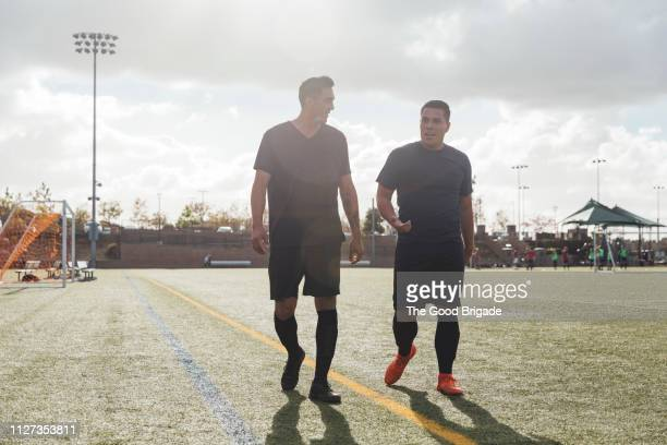 men walking and discussing on soccer field - only men stock pictures, royalty-free photos & images