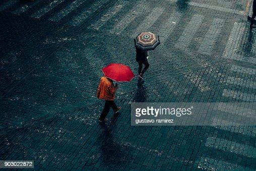 men walking in the rain with umbrella