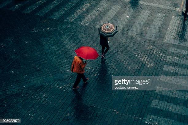 men walking in the rain with umbrella - regenschirm stock-fotos und bilder