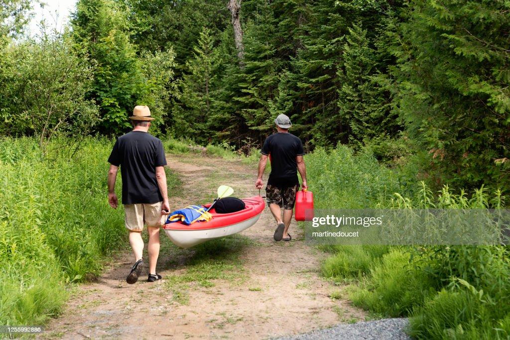 50 + men walking on dirt road with a kayak. : Stock Photo