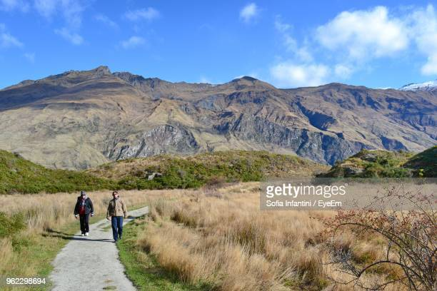 Men Walking On Footpath At Mountain Against Sky