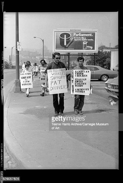 Men walking on sidewalk holding signs protesting against Port Authority Kentucky Fried Chicken Smirnoff and Italian Swiss Colony Wines with billboard...