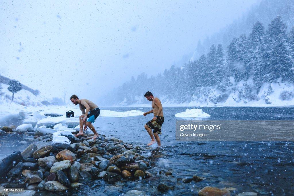 Men walking on stones in river during snowfall : Stock Photo