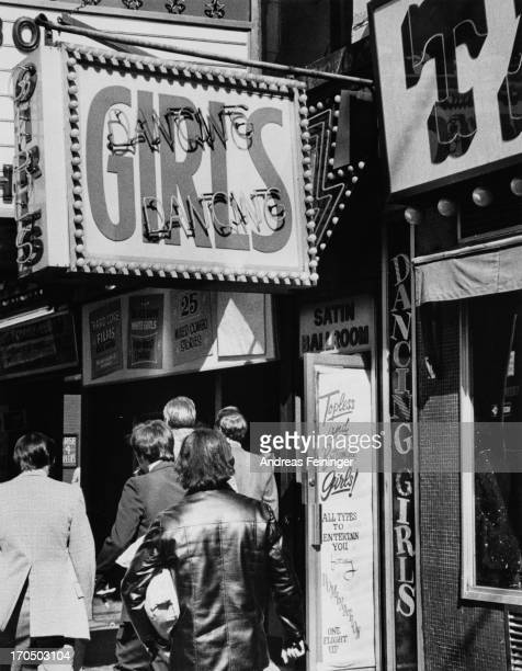 Men walking past the entrance to one of the strip clubs around Times Square New York City circa 1975