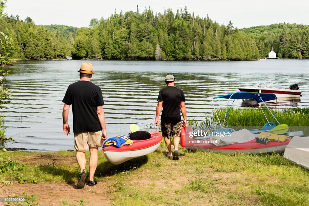 50 + men walking toward lake with a kayak. : Stock Photo