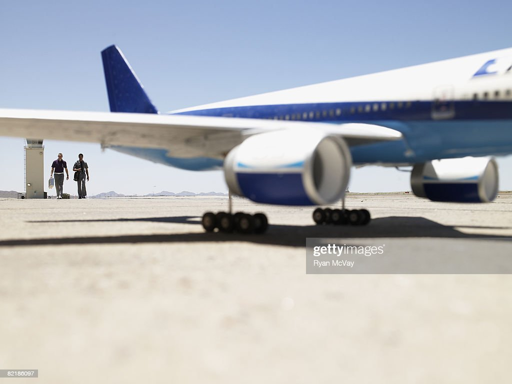 2 men walking toward plane : Stock Photo