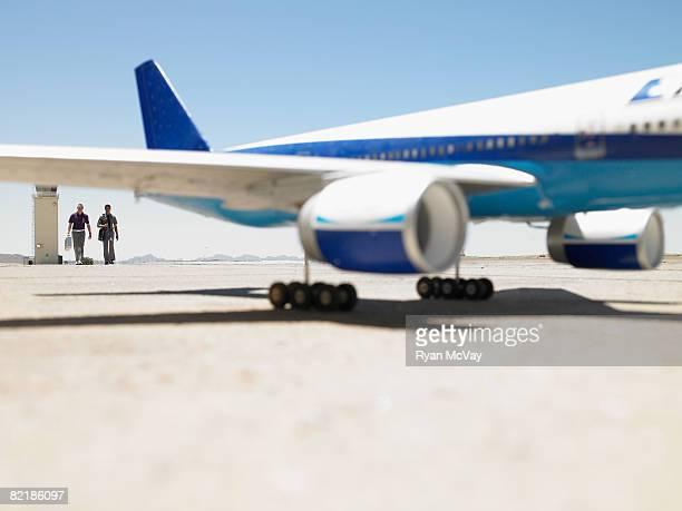 2 men walking toward plane