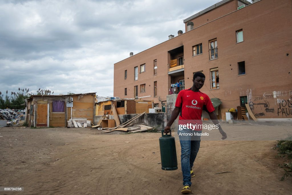 A men walks outsidean occupied building on October 4, 2017 in Rome, Italy . Since 5 years, hundreds of people, including Italians, Roma, Refugees and about 35 children live in a occupied building on the suburbs of Rome without electricity, toilet and surrounded by an abusive landfill.