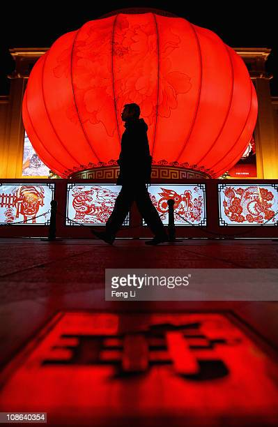 A men walks past a huge traditional red lantern for the upcoming Chinese Lunar New Year on Wangfujing shopping street on January 31 2011 in Beijing...
