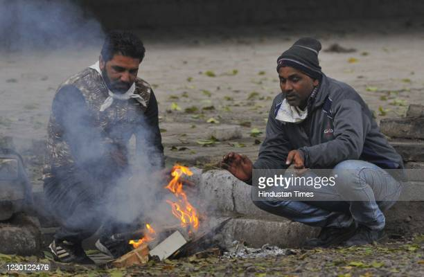Men warm themselves next to a bonfire on a cold winter morning at Sector 33, on December 13, 2020 in Chandigarh, India.