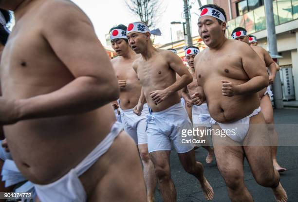 Men warm up as they prepare to take part in a purification ritual that involves pouring icecold water over themselves at Kanda Myojin shrine on...