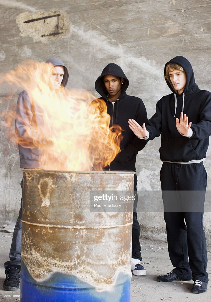 Men warming hands at fire in barrel : Stock Photo